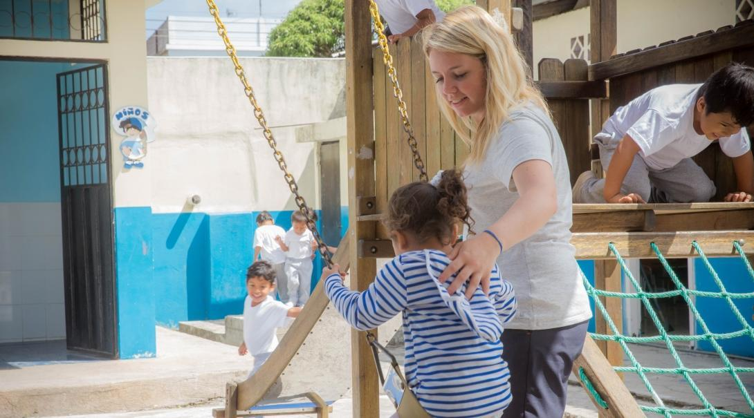 A teenage volunteer working with children in Ecuador pushes a child on the swing.